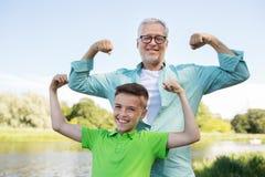 Szczęśliwy dziad i wnuk pokazuje mięśnie Zdjęcia Stock
