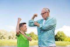 Szczęśliwy dziad i wnuk pokazuje mięśnie Zdjęcie Stock
