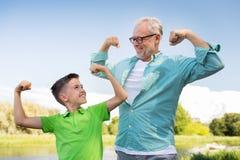 Szczęśliwy dziad i wnuk pokazuje mięśnie Fotografia Stock