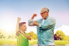 Szczęśliwy dziad i wnuk pokazuje mięśnie Zdjęcie Royalty Free