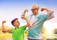Szczęśliwy dziad i wnuk pokazuje mięśnie Fotografia Royalty Free