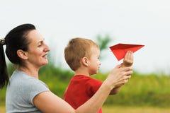 Szczęśliwy dzieciak bawić się z matką i zabawkarskim papierowym samolotem przeciw lata niebu Zdjęcia Royalty Free