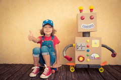 Szczęśliwy dzieciak bawić się z zabawkarskim robotem Zdjęcia Stock