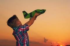 Szczęśliwy dzieciak bawić się z zabawkarskim samolotem na zmierzchu tle Fotografia Stock