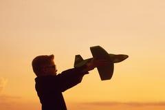 Szczęśliwy dzieciak bawić się z zabawkarskim samolotem na zmierzchu tle Obrazy Royalty Free