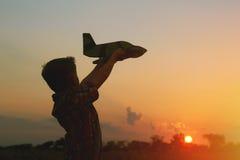 Szczęśliwy dzieciak bawić się z zabawkarskim samolotem na zmierzchu tle Zdjęcia Stock