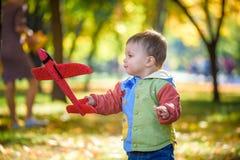 Szczęśliwy dzieciak bawić się z zabawkarskim samolotem przeciw błękitnemu lata nieba tłu Chłopiec rzutu piany samolot w parku lub zdjęcia royalty free