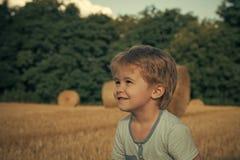 Szczęśliwy dzieciak ma zabawę Małe dziecko uśmiech przy polem z siano belami, rolnictwo Obrazy Stock