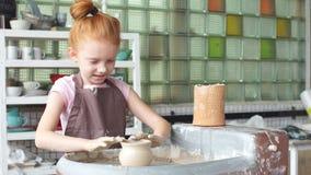 Szczęśliwy dzieciak Naciska Glinianą wazę na kole, dzieciak Pracuje przy Ceramicznym kołem Wolno i Pleśnieje wazę, blondynka Troc zdjęcie wideo
