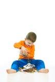 Szczęśliwy dzieciak rozlewa cukierki na podłogowym obsiadaniu Zdjęcia Stock