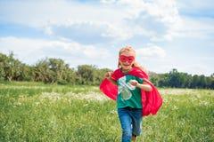szczęśliwy dzieciak w czerwonym bohater maski i przylądka bieg w łące obrazy stock