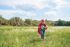 szczęśliwy dzieciak w czerwonym bohater maski i przylądka bieg w łące zdjęcie royalty free