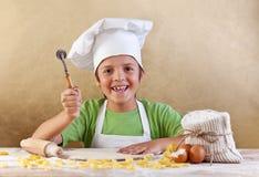 Szczęśliwy dzieciak z szefa kuchni kapeluszowym robi makaronem ciastkiem lub Fotografia Stock