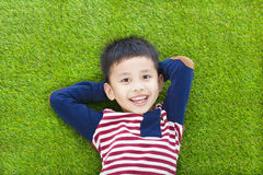 Szczęśliwy dzieciaka lying on the beach, mienie i jego głowa Zdjęcia Stock