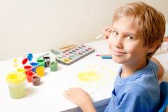 Szczęśliwy dzieciaka obraz z paintbrush i kolorowymi akwareli farbami Fotografia Stock