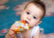 Szczęśliwy dziecka dziecka obsiadanie w krześle i je jedzenie od tubki ty dzieciak trzymał paczkę owocowy puree, gubi, w Obraz Royalty Free