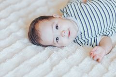 Szczęśliwy dziecka lying on the beach na bielu mieniu i prześcieradle ona nogi Figlarnie dziecka łgarski puszek w łóżku zdjęcia royalty free