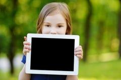 Szczęśliwy dziecka mienia pastylki pecet outdoors fotografia stock