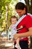Szczęśliwy dziecka obsiadanie w przewożenie temblaku. Obrazy Stock