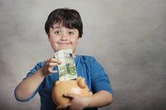 Szczęśliwy dziecka oszczędzania pieniądze w prosiątko banku Fotografia Royalty Free