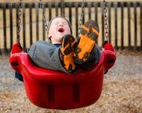 Szczęśliwy dziecko śmia się podczas gdy huśtający się Fotografia Royalty Free