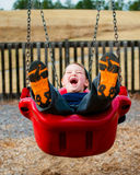 Szczęśliwy dziecko śmia się podczas gdy huśtający się Zdjęcia Royalty Free