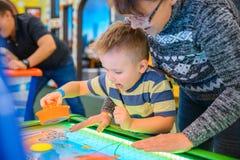 Szczęśliwy dziecko bawić się stołu lotniczego hokeja Obrazy Royalty Free