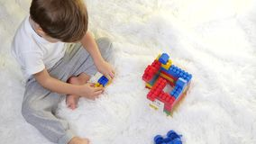 Szczęśliwy dziecko bawić się w barwionych blokach na podłoga na białym tle Dziecko zbiera konstruktora zbiory