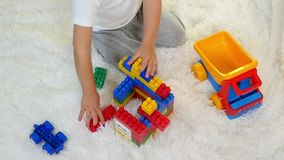 Szczęśliwy dziecko bawić się w barwionych blokach, siedzi na podłoga na białym tle Dziecko zbiera konstruktora w a zdjęcie wideo