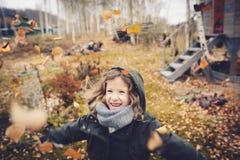 Szczęśliwy dziecko bawić się z liśćmi w jesieni Sezonowe plenerowe aktywność z dzieciakami Obrazy Royalty Free