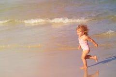 Szczęśliwy dziecko bieg, doskakiwanie w fala przy plażą i obraz stock