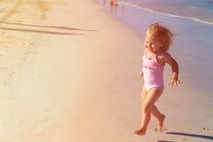 Szczęśliwy dziecko bieg, doskakiwanie w fala przy plażą i obraz royalty free