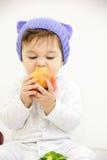 Szczęśliwy dziecko chłopiec obsiadanie w pieluszki i łasowania zielonych jabłczanych niebieskich oczach patrzeje kąt na bielu zdjęcia stock