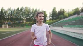 Szczęśliwy dziecko cieszy się bieg przy stadium mała dziewczynka jogging na lato wieczór zbiory wideo
