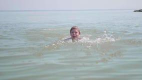 Szczęśliwy dziecko cieszy się dopłynięcie w morzu Wodna kiść, gorący letni dzień zbiory