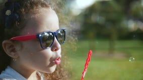 Szczęśliwy dziecko dmucha mydlanych bąble w parku swobodny ruch Akcyjny materiał filmowy zdjęcie wideo