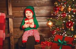 Szczęśliwy dziecko elfa pomagier Santa z prezentem przy choinką Obraz Royalty Free