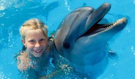 Szczęśliwy dziecko i delfiny w błękitne wody Zdjęcia Stock