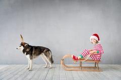 Szczęśliwy dziecko i pies na wigilii Obrazy Royalty Free