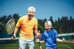Szczęśliwy dziecko i trener utrzymuje sporta wyposażenie obrazy royalty free