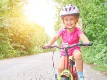 Szczęśliwy dziecko jedzie rower w plenerowym Obrazy Royalty Free