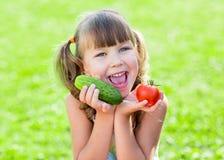Szczęśliwy dziecko na trawy pożyczce z zdrowymi warzywami Obrazy Stock