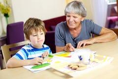 Szczęśliwy dziecko przygotowywający relaksować z ciastkami podczas pracy domowej Obraz Royalty Free