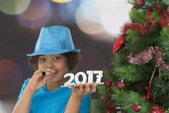 Szczęśliwy dziecko przyjaciel dmucha rogu nowego roku pojęcie w partyjnych chwyta drewna 2017 liczbach Obrazy Stock