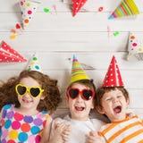 Szczęśliwy dziecko przyjaciel w karnawału przyjęciu, kłama na drewnianej podłoga Zdjęcia Royalty Free