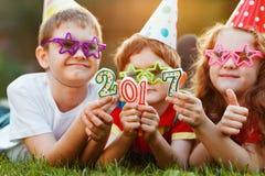Szczęśliwy dziecko przyjaciel w karnawału przyjęciu, kłama na zielonej trawie wewnątrz Obraz Stock