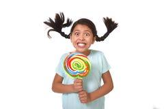 Szczęśliwy dziecko trzyma dużego lizaka cukierek z koników ogonami lata w dziwacznej szalonej śmiesznej twarzy Zdjęcia Royalty Free
