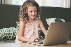 Szczęśliwy dziecko używa laptop w domu Szkolny dziewczyna uczenie z komputerem i internetem Obrazy Stock