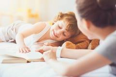 Szczęśliwy dziecko uczy się czytać z jego matką Fotografia Royalty Free
