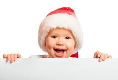 Szczęśliwy dziecko w Bożenarodzeniowym kapeluszu i pustym billboardzie odizolowywających dalej zdjęcie stock